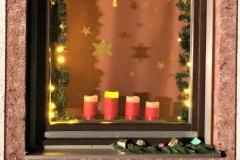 Passend zum Adventssonntag haben uns Klara und Norbert Gebert am zweiten Fenster mit Hilfe von zwei Geschichten und Liedern die Bedeutung des Advents näher gebracht und ihr Fenster mit dicken roten Kerzen gestaltet.