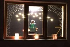 Eine beachtliche Menge an interessierten Zuhörern versammelte sich vor dem Fenster von Familie Bobinger. Dargestellt wird Abraham, der mit geöffneten Händen da steht und Gottes Auftrag annimmt. und somit ein leuchtendes Vorbild für Gottvertrauen ist. Symbolisch konnte jeder der Anwesenden seinen Namen auf einen Stern schreiben, der noch mit ins Fenster dekoriert wurde.
